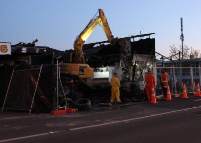 Work on demolishing shops on High Street went on after sunset.